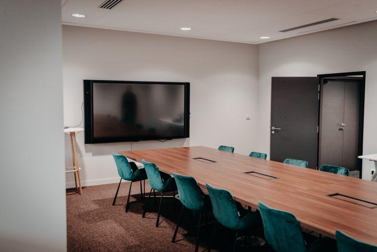 Salle de réunion VIP avec 14 chaises bleus autour d'une grande table en bois
