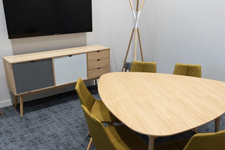 Salle de réunion vide avec une table, 6 chaises et une télévision