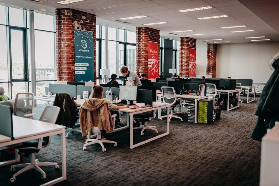Open space de la start-up Webreathe, plusieurs bureaux avec des personnes qui travaillent